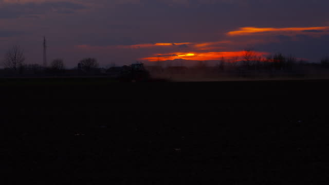 Tractor plowing the field at sunset