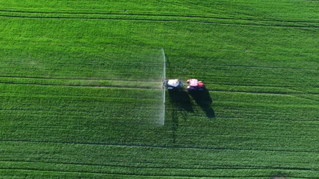 Tractor Spraying Crop Field In Spring Flyover