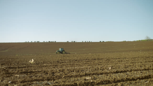Tractor towing plow through fallow field