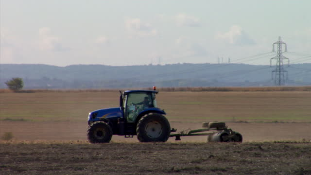 WS TS Tractor with harrow crossing ploughed field, Rochester, Kent, United Kingdom