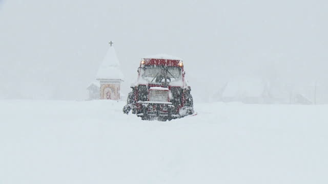 HD SLOW-MOTION: Tractor with plow in snowfall
