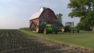 WS PAN Tractors parked next to barn and field of crops, Newark, Illinois, USA