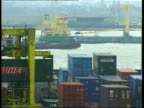 Trade balance of payments deficit increases aNAT TMS Gantry crane moving container as boats passing on river in b/g TMS Worker attaching crane ropes...