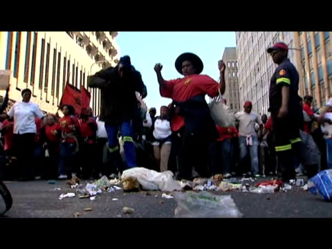 Trade unionists and council workers kick rubbish along streets in protest over poor wages during anti government demonstration Johannesburg 27 July...