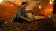 Trader bags up dried fruit and nuts at market, Morocco Available in HD.