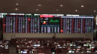 Traders talk in front of an electronic board displaying stock figures and currency exchange rates on the floor of the Philippine Stock Exchange in...
