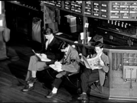 Trading posts on trading floor 'page boys' in 'c' armbands w/ paperwork WS Women in uniforms walking through doorway Men in suits entering building...