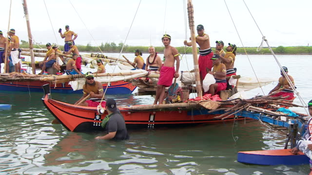 Traditional sailing vessels arriving in Guam for the 12th Festival of Pacific Arts with man in welcoming party bearing smoking torch