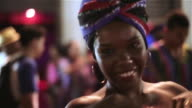 Traditional samba dancer moves to the rhythm of the drumline and smiles at camera