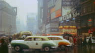 1953 WS traffic and pedestrians in rainy Times Square / New York City