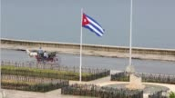 Traffic and pedestrians move along the historic Malecon oceanfront boulevard January 24 2015 in Havan Cuba