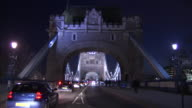 Traffic and pedestrians move along Tower Bridge at night.