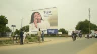 Traffic and pedestrians pass an advertisement for Tigo telecommunication services in N'Djamena Chad on Wednesday Aug 16 2017