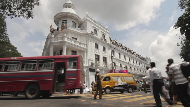 MS T/L Traffic and people passing the historic Queens Hotel / Kandy, Central Province, Sri Lanka