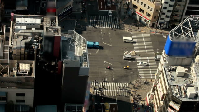 Traffic and people passing through busy intersection of Tokyo