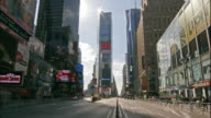 Traffic and people travel on Broadway and Seventh Avenue in Times Square.