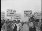 Traffic and strikers outside the North American Aviation Plant / Striking workers at plant gate / long shot of workers gathered outside of plant /...