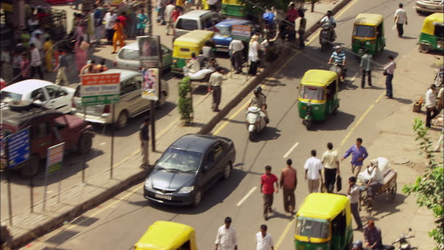 Traffic approaching fountain at junction on busy street in New Delhi, India. Available in HD.