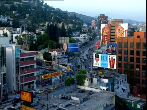 Traffic buildings and billboards on Sunset Strip early evening light Hollywood