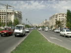 Traffic drives along narrow part of Unirii Boulevard Ceaucescu's Palace in distance Bucharest