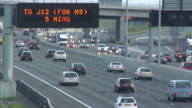 HA WS Traffic driving below junction sign on M25 Motorway in early evening / London, England