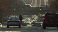 Traffic driving on 3rd avenue in the bronx near I95 late in the day as pedestrians cross the street