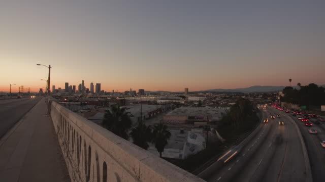T/L HA WS Traffic driving on Los Angeles Freeway under 6th St Bridge at dusk / Los Angeles, California, USA