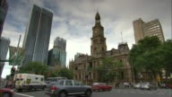 Traffic flows through Town Hall Junction on a cloudy day in Sydney, Australia.