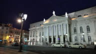 WS Traffic in front of National Theatre D. Maria II illuminated at night / Lisbon, Portugal