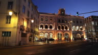 WS Traffic in front of Rossio railway station illuminated at dusk / Lisbon, Portugal