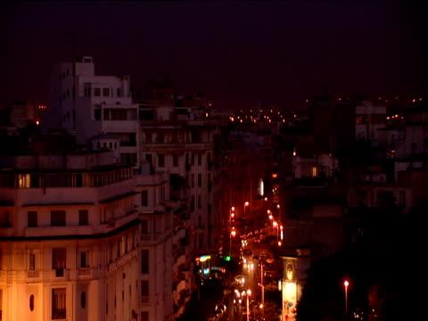 Traffic in street between high white buildings in evening light Casablanca