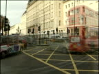 Traffic including buses and black cabs moving across junction in Whitehall