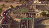 AERIAL ZO Traffic lined up at border crossing at US/Mexican border crossing and cityscape with Mexican flag, Juarez, Chihuahua, Mexico