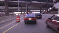 Traffic merges to a single lane under overpasses.