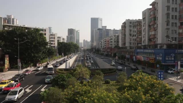 Traffic move along a road past commercial and residential buildings in Guangzhou China on Monday Oct 30 2017