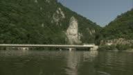 Traffic moves across a bridge over the Danube River, passing the sculpture of Decebalus, Romania.