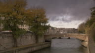 Traffic moves across a small bridge on the River Seine. Available in HD.