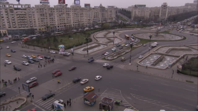 Traffic moves around a large roundabout in front of the Palace of Parliament in Bucharest. Available in HD