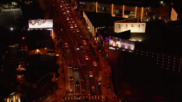 Traffic moves east over Sunset Boulevard, at night in West Hollywood, California.