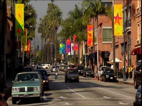 Traffic moves towards camera down Rodeo Drive with palm trees in background. Colorful signs on side of shops