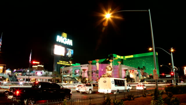 Traffic moving along on East Tropicana Avenue lights flashing of MGM Grand marquee hotel casino building BG NV