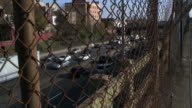 Traffic moving both ways on the cross bronx expressway during the day in the bronx being shot through a grungy, rusted and warped chain link fence