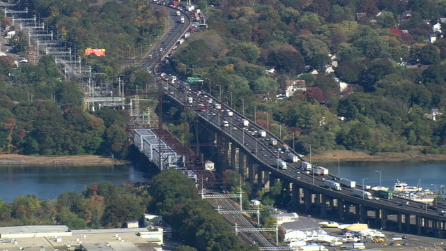 WS AERIAL Traffic moving on bridge surrounded by nesting in trees / Connecticut, United States