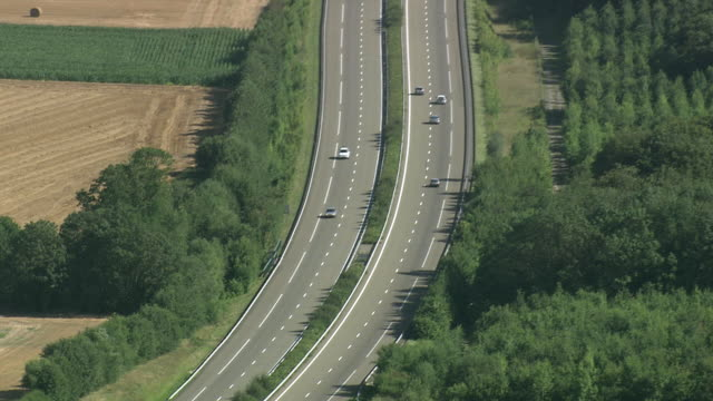WS AERIAL ZI ZO PAN TS Traffic moving on motorway through farm field / Picardy, France
