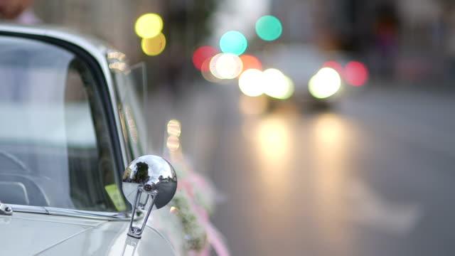 Mezzo colpo movimento passato a fuoco selettiva traffico bianco auto matrimonio vintage decorato per