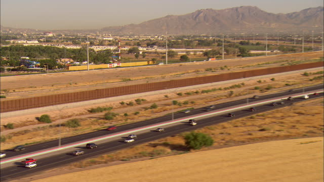 AERIAL Traffic on Border Highway along new border 'wall', El Paso, Texas, USA