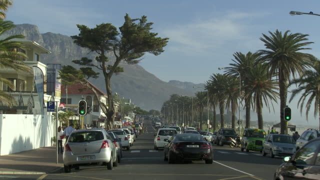 WS PAN Traffic on Camps Bay boulevard with Twelve Apostles mountain in background, Cape Town, Western Cape, South Africa