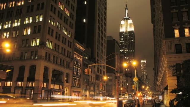 WS T/L TD Traffic on city street with Empire State Building in background at night / New York City, New York, USA.