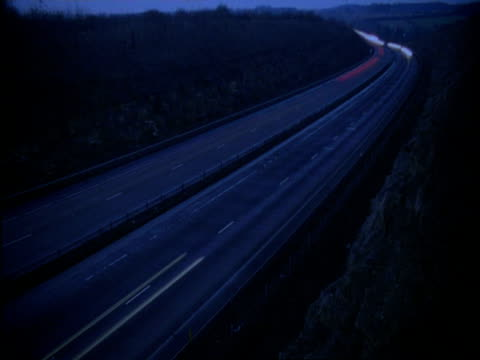 T/L traffic on road through mountain as night falls, A38 Devon, England