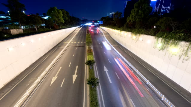 Traffic on road to tunnel in modern city  at night,time lapse.